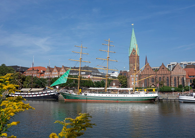 """Side view of the tall ship """"Alexander von Humboldt"""" on the Weser. The St. Martini Church can be seen in the background."""