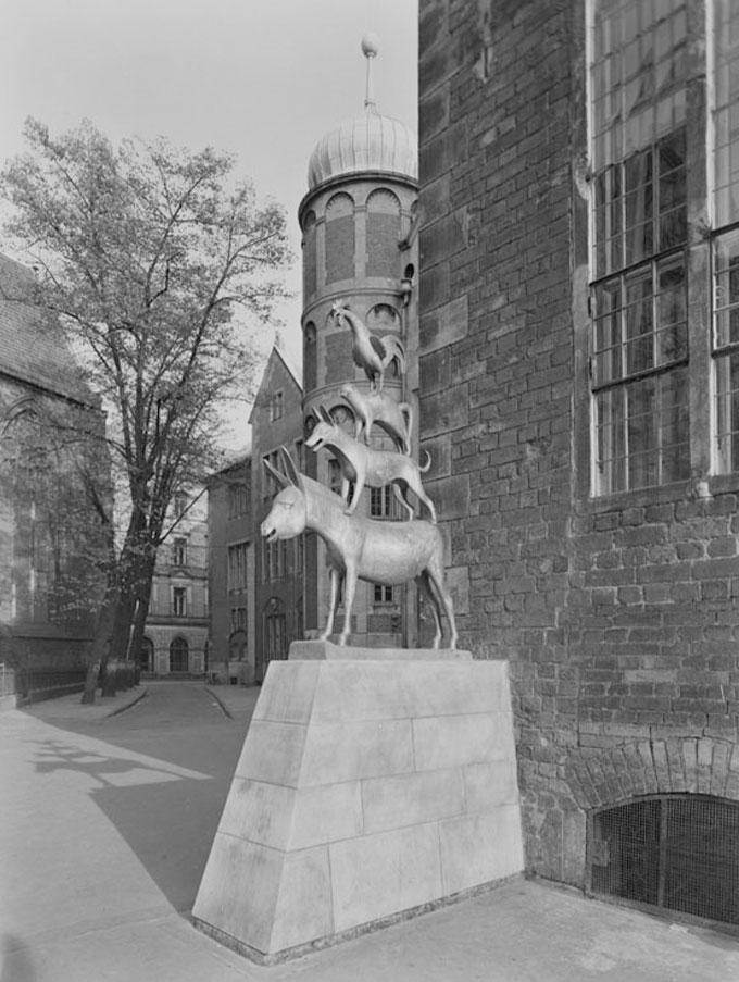 """Historische Seitenansicht der """"Bremer Stadtmusikanten"""". Im Hintergrund ist die Unser Lieben Frauen Kirche zu sehen."""