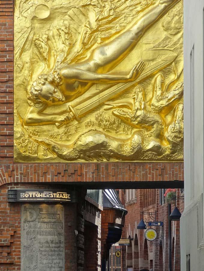 Ein großförmiges Bronzerelief zeigt einen unbekleideten jungen Mann, der mit einem Schwert gegen ein dreiköpfiges Wesen kämpft. Es ziert den Eingang der Böttcherstraße, welche man im Hintergrund sehen kann.