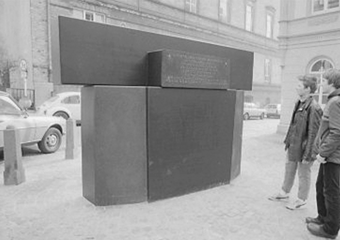 Two passerby look at the memorial for the victims of the November pogroms in 1938. The cubic memorial bears a plaque with the names of the murdered people.