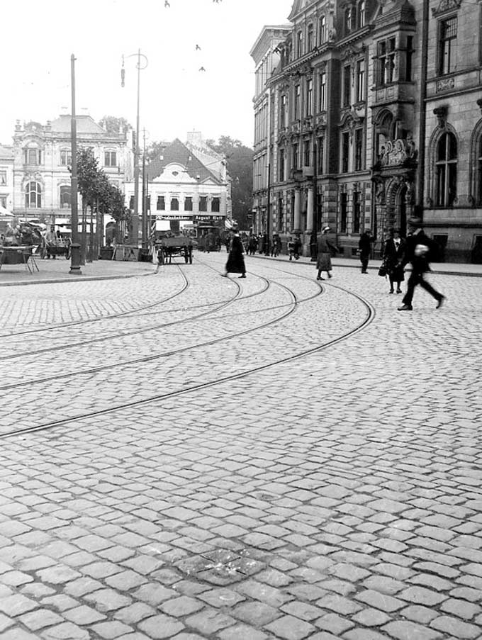 Historical view of the spitstone. Tram switches and passerby can be seen in the background. The view is directed to the Domshof.